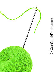 Green thread ball and needle with pink thread isolated on white