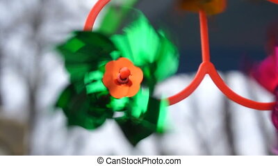 Green toy windmill is spinning from the wind