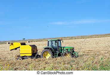 green tractor in hay bale field