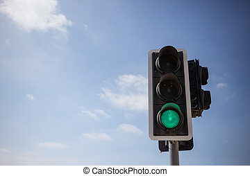 Green traffic light. Blue sky with few clouds background. ...