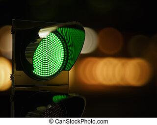 Green traffic light in the dark night city street