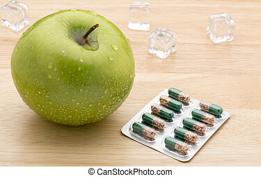 Green transparent pills capsules and fresh green apple