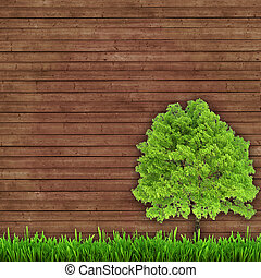 green tree and fresh grass on a wooden background