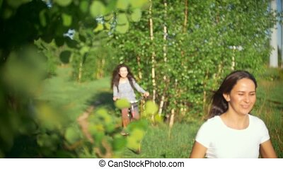 Green tree branches, girls laughing and catching up with...