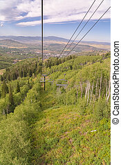 Green trees and grasses on a mountain with chairlifts on a cloudy summer day