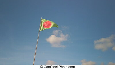 Green triangle flag with red dot fluttering in the wind against blue sky at a beach in Anglet, France. It indicates a surfing area.