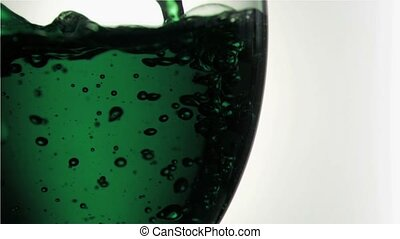 Green trickle in a super slow motion filling a glass against...