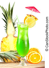 Green tropical cocktail with pineapple, orange and lime slices