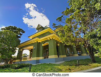 Green tropical house against blue sky - View of beautiful...