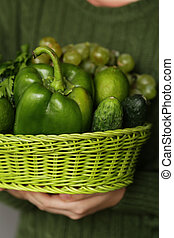 green vegetables and fruits in a wicker basket