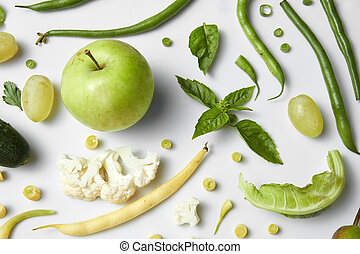 Green vegetables and fruits isolated on white.