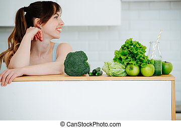 Green vegetables, apples and smoothies against the backdrop of young girl