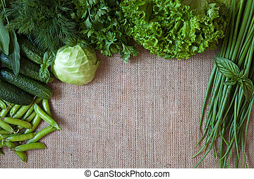 Green vegetables composition frame on rustic sackcloth background. Peas, cabbage, cucumber, basil, dill, onion,