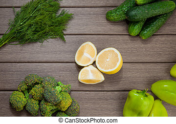 Green fresh vegetables and spice on wooden background