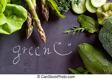 Green vegetables on black slate with inscription word green.