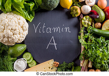 Green vegetables rich in vitamin A on black slate.