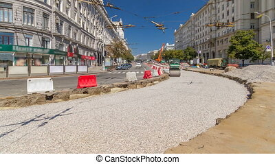 Green vibration roller compactor rolls on a stones at road...