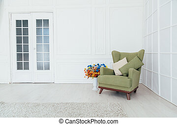 green vintage chair in the interior of an empty white room