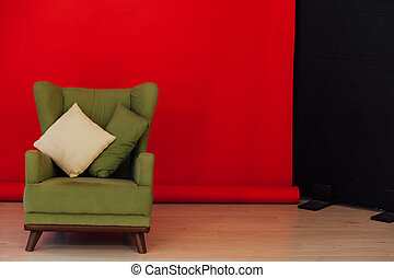 green vintage chair in the interior of the red black room