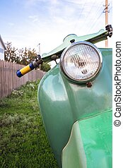 Green vintage scooter in grass - Green vintage scooter...