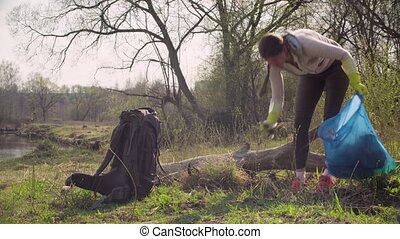 Green volunteer collecting garbage in the forest - Woman...