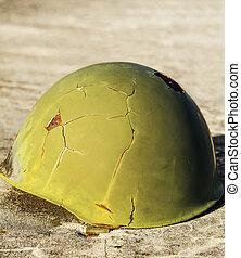 Green war helmet - Green helmet used in war, placed on a...