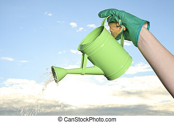 Green watering can on the hand of a girl
