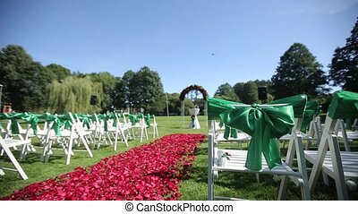 Green wedding chairs in an open ceremony with flowers and ornaments
