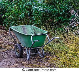 green wheelbarrow in a garden, working on garden maintenance, equipment for the backyard