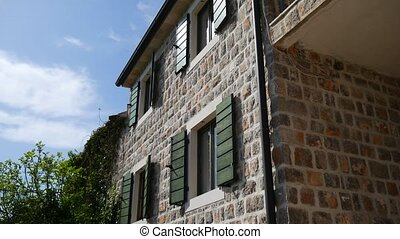 Green window shutters. The facade of houses in Montenegro