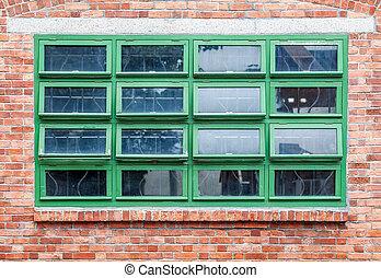 Green windows on a brown brick wall