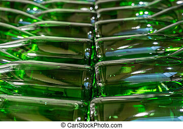 Green wine bottles filled with white wine stacked on top of each others
