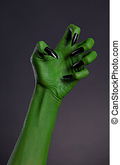 Green witch hand with sharp black nails, real body-art