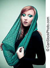 Green woman. Woman wearing green scarf with green makeup.
