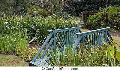Green Wood Bridge in formal Garden - A small green wooden...