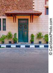 Green wooden door with red tile canopy above and green window shutters on stone bricks wall