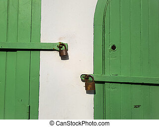 Green wooden doors with padlocks on white hay.