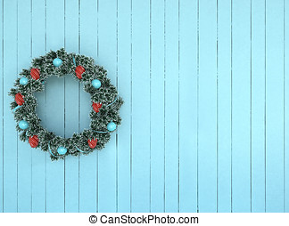 Green wreath with blue and red bow on antique teal aqua rustic wood