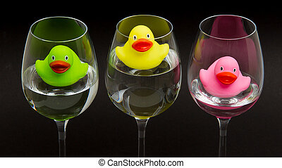 Green, yellow and pink rubber ducks in wineglasses