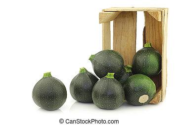 Green zucchini's (Cucurbita pepo) in a wooden crate