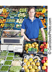 Greengrocer - A greengrocer standing behind the display...