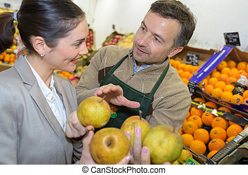 Greengrocer advising customer about apples