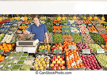 Greengrocer at work - A green grocer weighing vegetables in ...