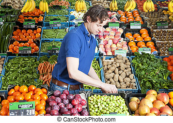 A greengrocer at work amidst various crates of fresh fruit and vegetables in a shop