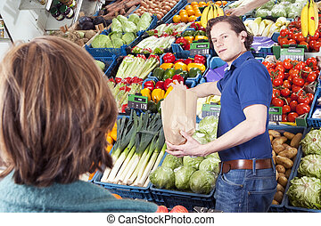 Greengrocer - Green grocer serving a customer, filling a ...