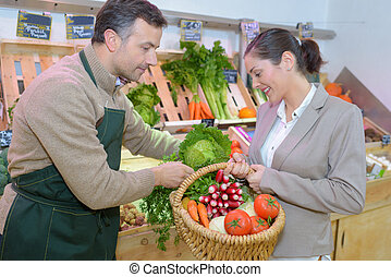 greengrocer helping customer with her shopping