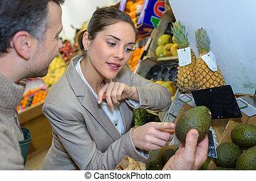 greengrocer helps customer choose avocado