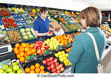 Greengrocer serving a customer - Green grocer serving a ...