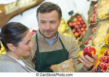 Greengrocer serving apple to customer