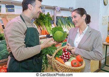 Greengrocer serving customer